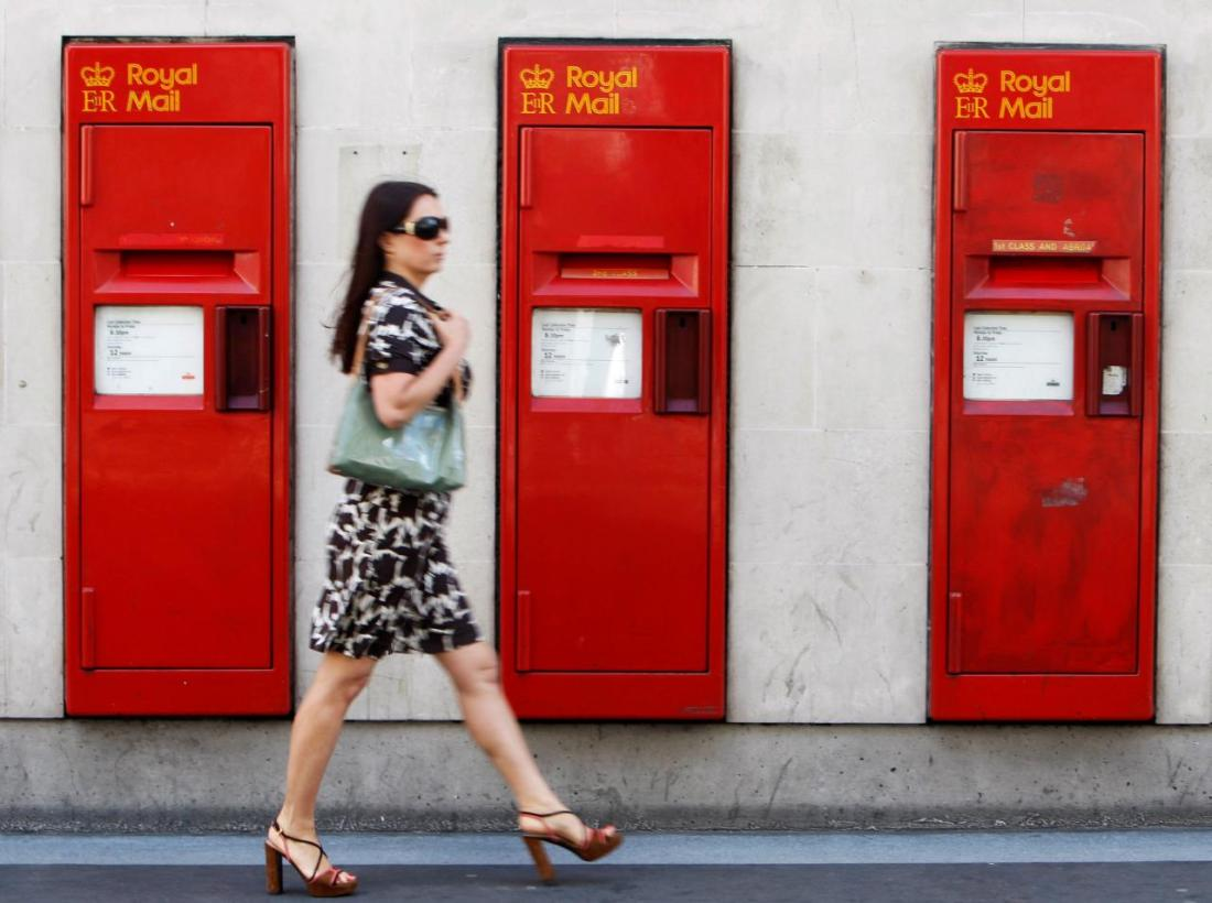 FILE PHOTO: A woman passes a row of Royal Mail post boxes in London